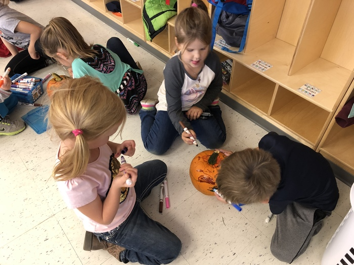 Teamwork decorating pumpkins